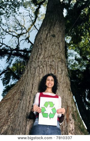 Recycling: Woman In Front Of A Tree Holding A Recycle Sign