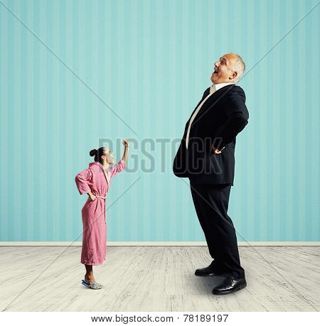 angry small woman screaming at big laughing senior man