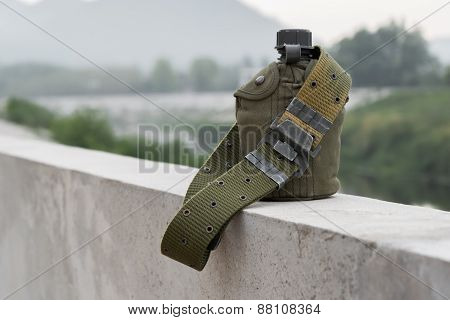 Army water canteen with a Cartridge belt on bridge bar at riverside.