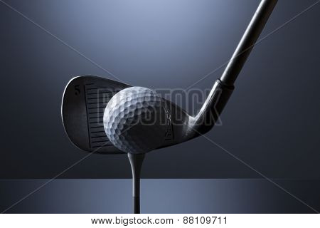 Golf ball on tee and club isolated on dark blue background.