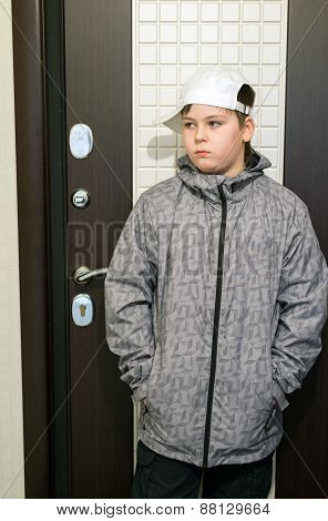 Boy Standing At  Front Door Of The House