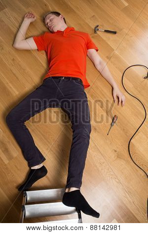 Young man on the floor having dangerous accident at home poster