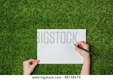 Writing on blank sheet of paper over green grass