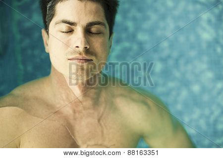 Young Man Floating In The Swimming Pool