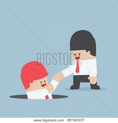 Businessman Helping His Friend By Take Him Out From The Hole