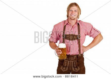 Bavarian man with leather trousers (lederhose) holds oktoberfest beer stein in hand.