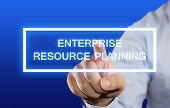 Business concept image of a businessman clicking Enterprise Resource Planning button on virtual screen over blue background poster