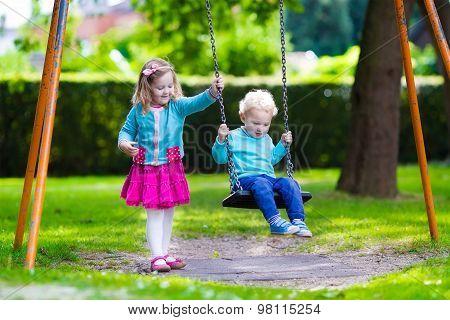 Kids On Playground Swing