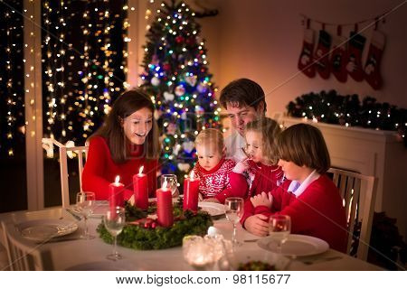 Big family with three children celebrating Christmas at home. Festive dinner at fireplace and Xmas tree. Parent and kids eating at fire place in decorated room. Child lighting advent wreath candle. poster