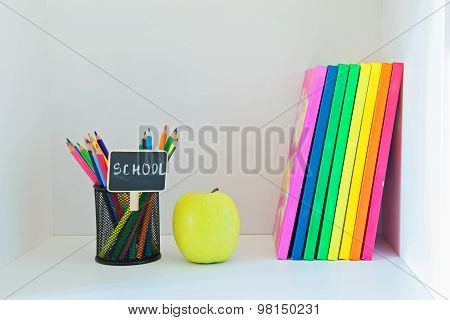 Yellow apple, pencils in holder and multi colored books