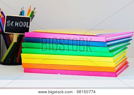 Multi colored books in stack on the light-coloured bookshelf