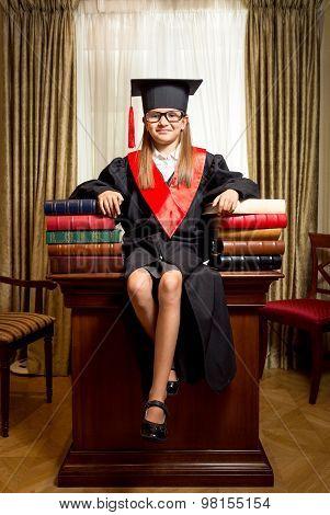 Girl In Graduation Cap Sitting On Desk Between Piles Of Book