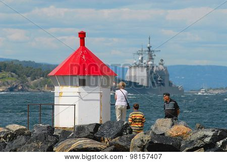 People watch military ship passing by the fjord in Frogn, Norway.