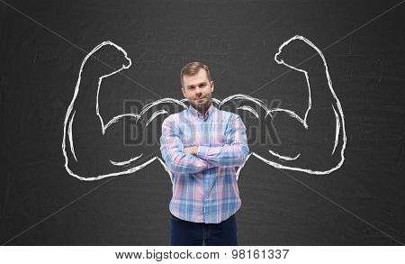 Young Handsome Man In Casual Shirt With Drawn Powerful Hands. Black Chalkboard Background.