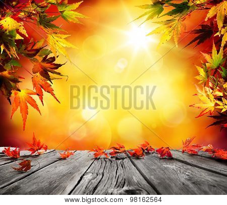 Autumn background with red falling leaves on wooden plank