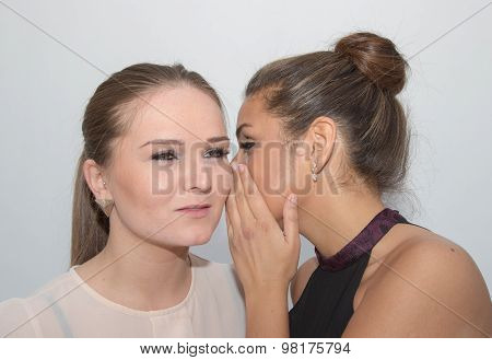 Girl whispering a secret in another girl's ear poster