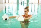 Blond young woman doing aqua aerobics with foam dumbbells in swimming pool at the leisure centre poster