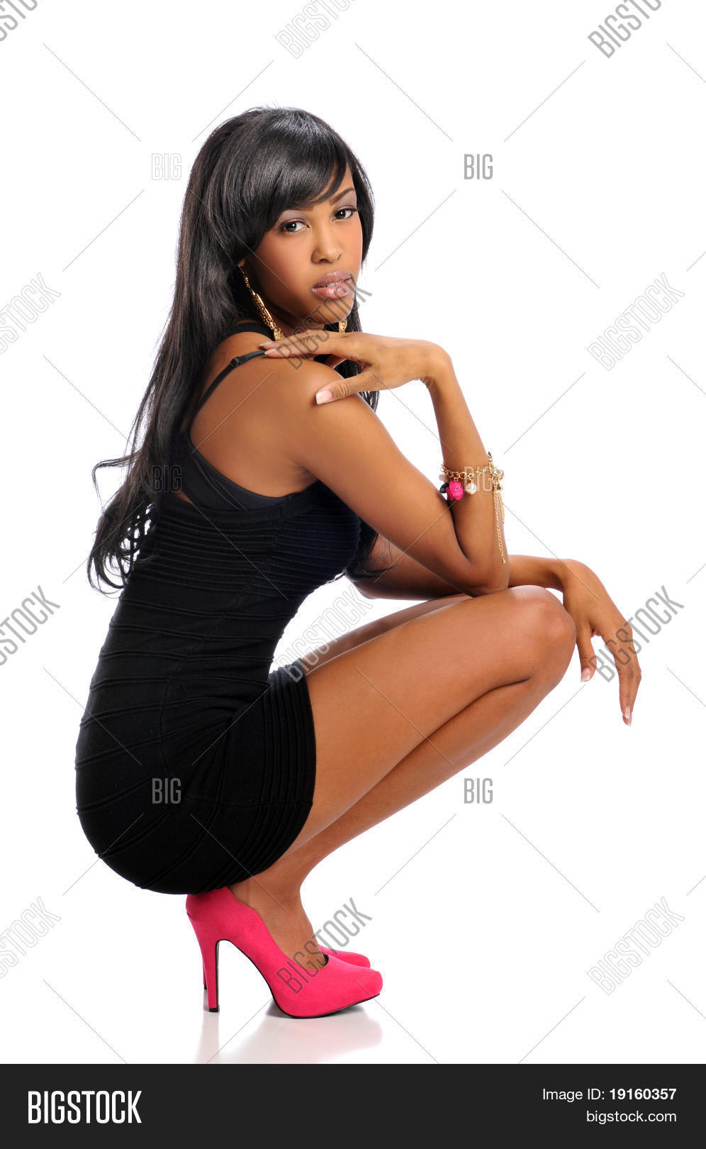 91590a5e91bc6 African American woman posing wearing a black dress and high heels