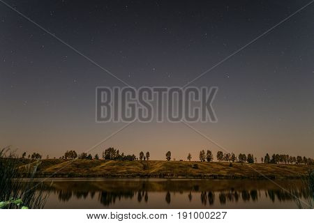 Starry night over the lake. Night landscape.