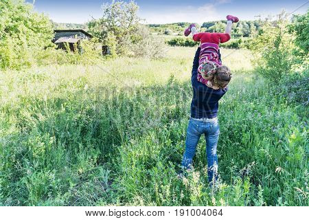 Woman throws her child upside down among the grass with forest in the background