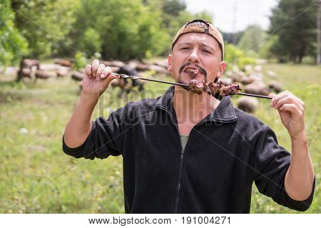 Bearded man in a cap eats meat from a skewer against the background of a herding herd of sheep