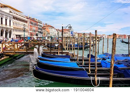 Venice Italy - June 14 2016: Gondoloa boats lined up in the harbor in Venice Italy. Visitors pack St. Marks Square for tours and boat rides.