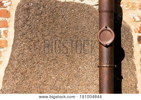 View of a red-brick exterior wall with brown drainpipe - for background purposes