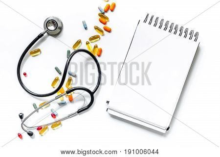 Medical things with notebook on white background top view composition with phonendoscope and drugs.