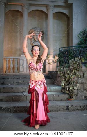 Beautiful woman in a pink dress decorated with pearls performs Arabic dance