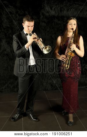 Man and woman playing on wind instruments in a black room