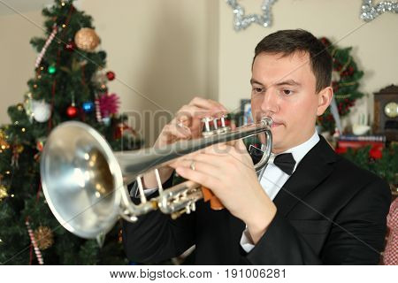 Portrait of a trumpeter before a Christmas tree