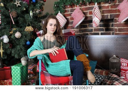 A young girl in a knitted cardigan with a red book in her hands sits on a chair near the New Year tree with gifts