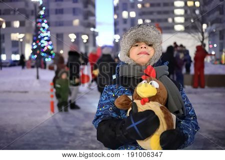 Portrait of a little boy in a fur hat with a toy cock in his hands in the yard in winter