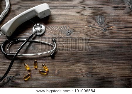 phone handset, pills and phonendoscope on dark wooden desk top view make appointment with a doctor.