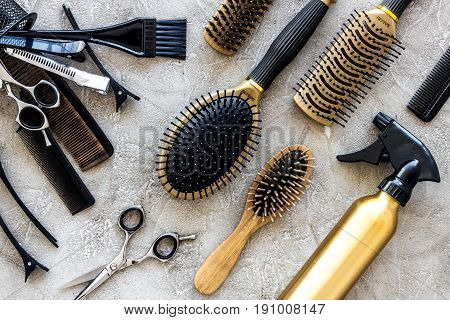 Combs and hairdress tools on stone table background top view.
