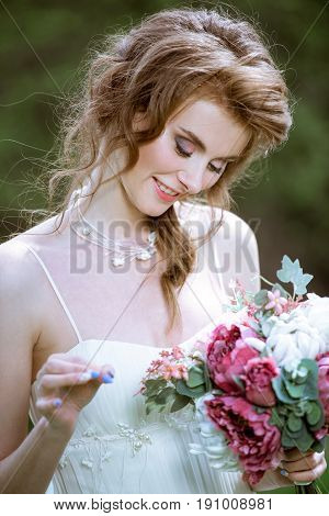 Blonde bride in fashion white wedding dress with makeup. Wedding day of bride in bridal gown. Beauty woman and bouquet. Fashion blonde model outdoors. Portrait beauty model in white bridal dress