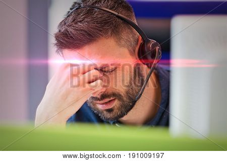 Tired mid adult businessman wearing headset while pinching bridge of nose at office