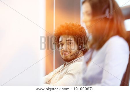 Portrait of young businessman using telephone headset with colleague in foreground in office