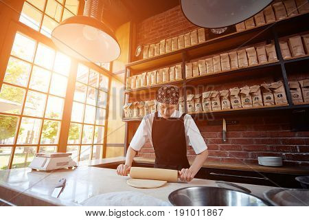 Smiling woman rolling dough with pin in the kitchen of restaurant. Horizontal indoors shot. Cheerful woman working with rolling pin. Making pasta. Making pasta in restaurant.