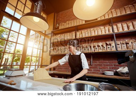 Woman working with rolled knead. Horizontal indoors shot of female cook working with roll of dough for pasta. Making pasta. Making pasta in restaurant.