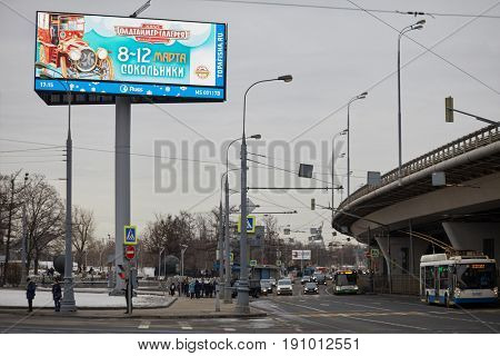 MOSCOW, RUSSIA - FEB 28, 2017: Street traffic on crossroad near overpass and advertising billboard with information about Oldtimer Gallery exhibition.