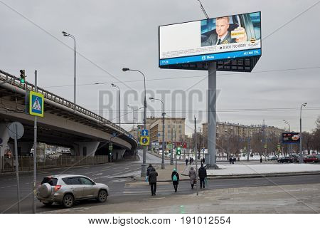 MOSCOW, RUSSIA - FEB 28, 2017: Street traffic on crossroad near overpass and advertising billboard with information about Beeline cell operator.
