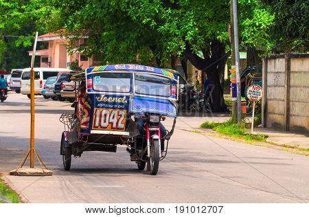 Dumaguete Philippines - 13 May 2017: National Philippine transport tricycle on city street. Tourist transport. Transport traffic in Philippines. Traditional transport. Custom motorbike. Green city
