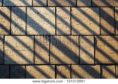 Railing Shadow Lines Across Concrete Paving Block Stones