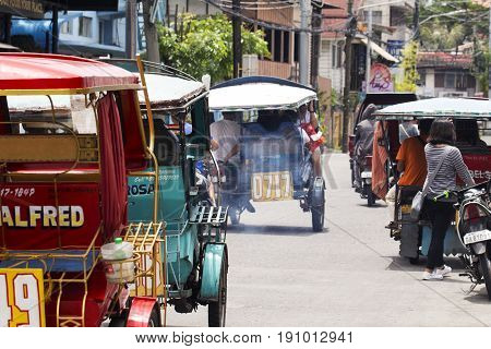 Dumaguete Philippines - 13 May 2017: city street view with local people and tricycles. Tropical country lifestyle. Tropical travel destination. Tourist transport. Transport and traffic in Philippines