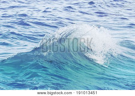 Turquoise blue wave on rippled sea water. Sea water closeup photo. Sea wave swirl. Surfing in seashore. Clean wave splash. Seaside vacation concept. Marine scene or background. Wave curl with spray