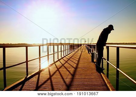 Alone Man On Pier And Look Over Handrail Into Water. Sunny Clear Sky, Smooth Water