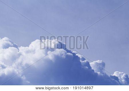 Big cloud on blue sky. Cloudscape photo background. Romantic skyscape with raincloud. Stormy cloud on sunny sky. Climate or weather change. Tropical rain season. Moisture banner. Fluffy cotton cloud