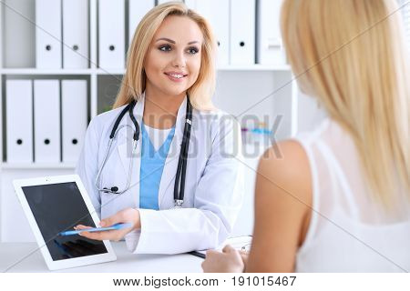 Doctor and  patient  discussing something while phisician pointing into laptop computer. Medicine and health care concept