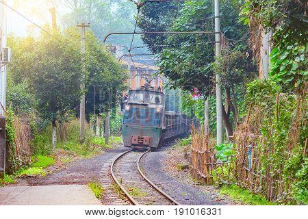 Yuejin Jiayang Mining Region Sichuan province China November 05 2016: Electric narrow-gauge locomotive with the freight train moves through Yuejin town.